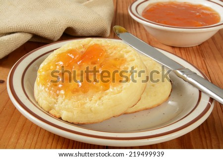 Hot buttered crumpets with apricot jam on a rustic wooden table - stock photo