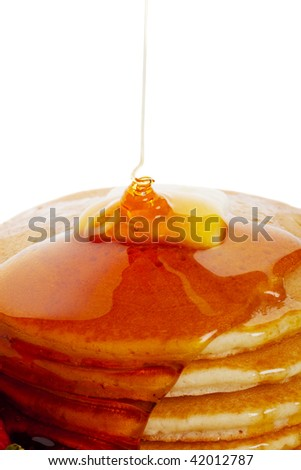Hot buttered pancakes with maple syrup drizzling down onto the stack. - stock photo