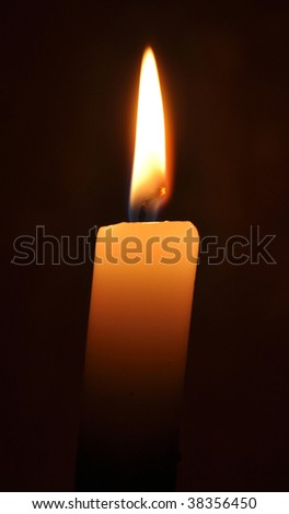 Hot candle in a dark room near-by
