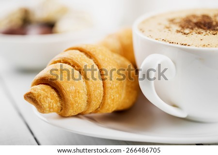 Hot cappuccino and pastries on white wooden boards - stock photo