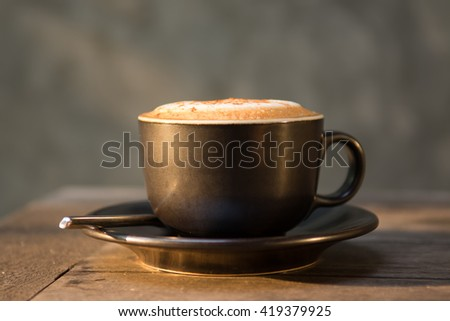 Hot cappuccino coffee cup on wooden table agent sunlight in morning time