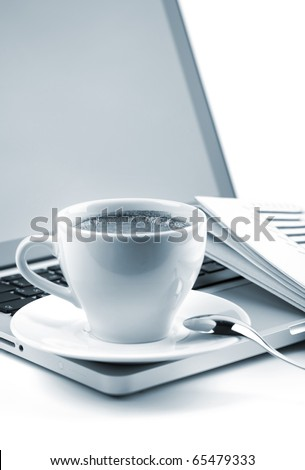 Hot cappuccino cup on laptop and newspaper. Blue toned - stock photo