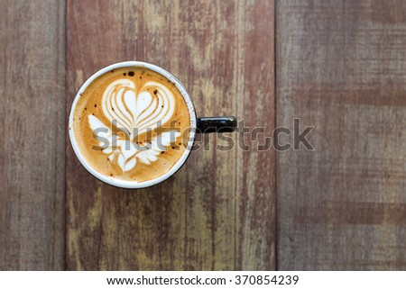 Hot cappuccino in black ceramic cup with beautiful latte art on wooden table. - stock photo