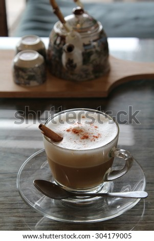 Hot cappuccino with frothed milk in clear cup on wooden table. - stock photo