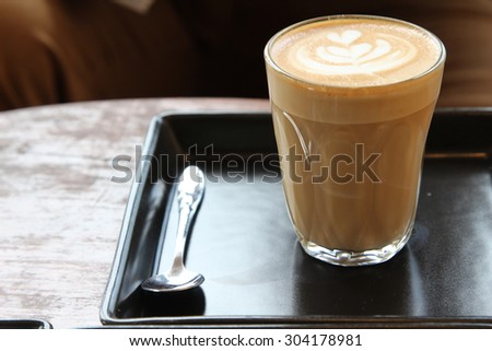 Hot cappuccino with frothed milk in clear glass on black plate. - stock photo