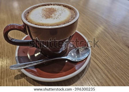 Hot cappuccino with high contrast effect in a mug on wooden table - stock photo