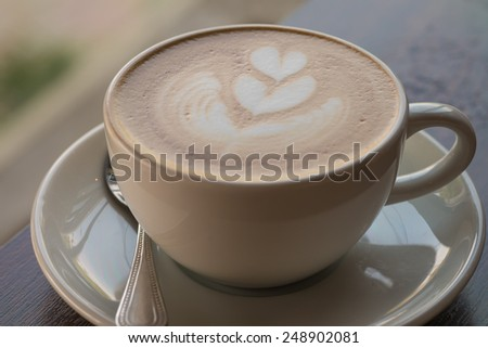 Hot cappucino coffee with heart on top in white cup on wood table. - stock photo