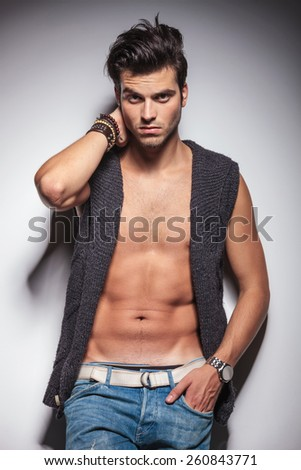 Hot casual man posing with one hand in his pocket while leaning on a wall. - stock photo