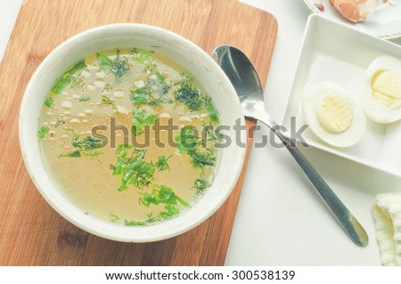 Hot chicken soup in bowl, spoon, eggs, eggshell and cloth napkin on rustic wooden table - stock photo