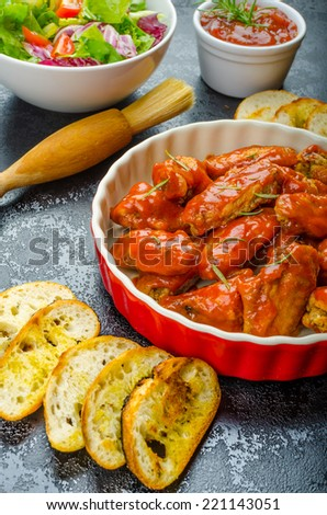 Hot chicken wings with spicy habanero sauce and mixed salad with cherry tomatoes, grilled baguette with olive oil - stock photo