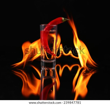 Hot chili pepper in a  shot glass with a fire on a black background