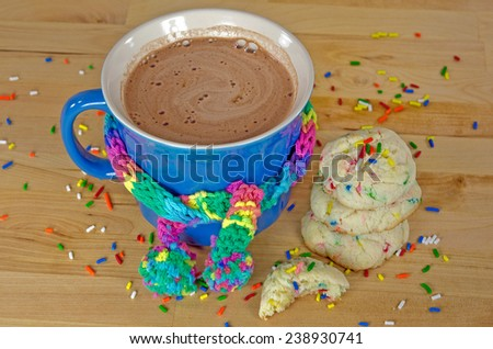 hot chocolate drink in blue mug with colorful winter scarf and cookies  - stock photo