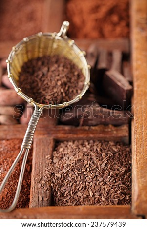 hot chocolate flakes  in old rustic style silver sieve on wooden spicy box, shallow dof - stock photo