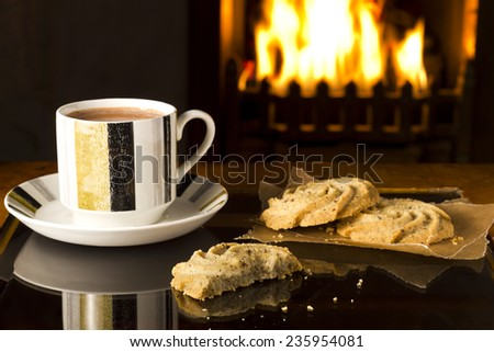 Hot chocolate in a cup and saucer, with partially eaten biscuits, in front of a warm fireplace