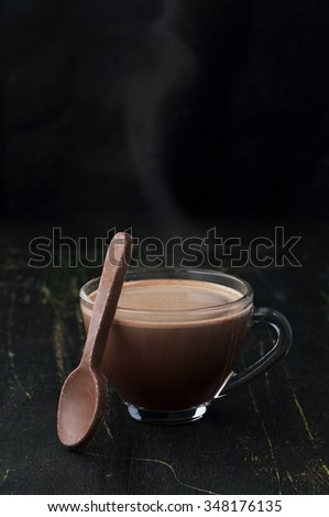 hot chocolate in a glass cup and eatable chocolate spoon on a black wooden table