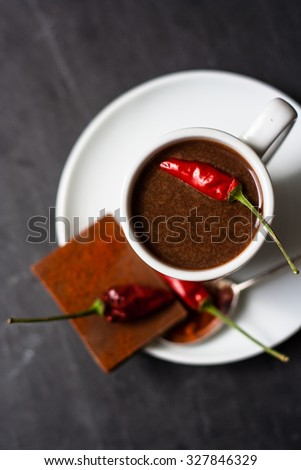 Hot chocolate in a white cup and red chili peppers on a dark stone background
