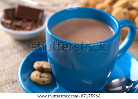 Hot chocolate in blue cup with cookies on saucer and chocolate in the back (Selective Focus, Focus on the front of the cup) - stock photo