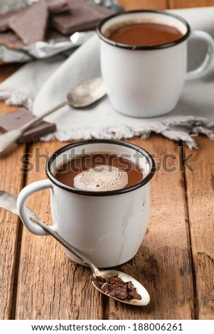 Hot chocolate in two enamel mugs on a wooden table - stock photo