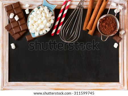 Hot chocolate mix on old chalk blackboard. Sweet marshmallow, chocolate bars, sugar, cocoa powder, cinnamon, and whisk for cooking winter holiday drink. - stock photo