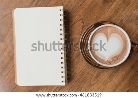 Hot chocolate on wooden table and note book.