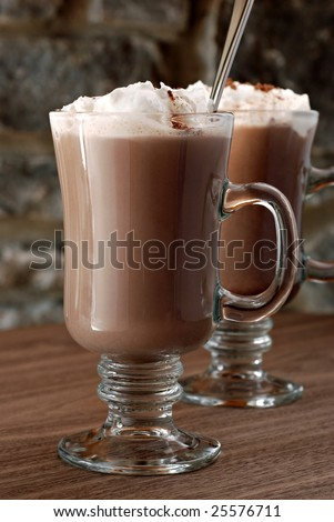 Hot chocolate or coffee latte in irish coffee mugs with stone wall in background.  Macro with extremely shallow dof. - stock photo