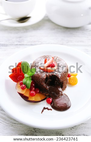 Hot chocolate pudding with fondant centre with fruits, close-up - stock photo