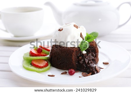 Hot chocolate pudding with fondant centre with ice-cream, close-up - stock photo