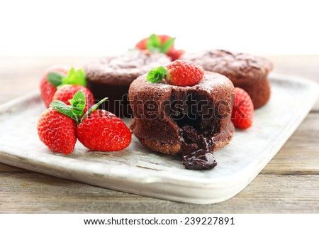 Hot chocolate pudding with fondant centre with strawberries, close-up - stock photo