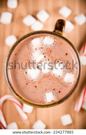 Hot Chocolate - This is a shot of a hot cup of hot chocolate with marshmallows and a candy cane setting nearby. Shot directly overhead.  - stock photo