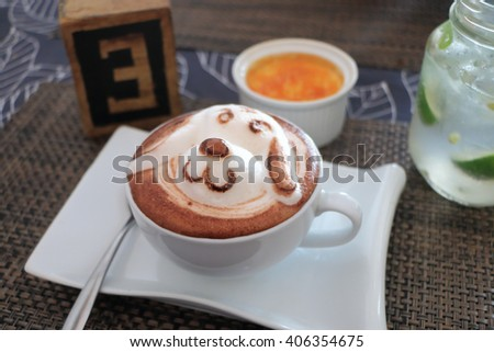 Hot chocolate with latte art in white cup on the table  - stock photo