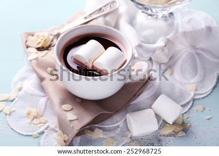 Hot chocolate with marshmallows in mug, on color wooden background