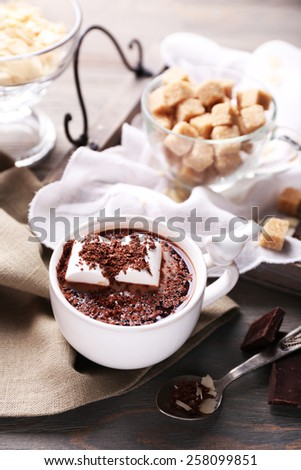 Hot chocolate with marshmallows in mug, on tray, on color wooden background - stock photo
