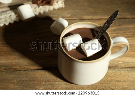 Hot chocolate with marshmallows in mug, on wooden background - stock photo