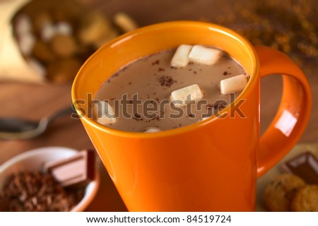 Hot chocolate with marshmallows in orange cup surrounded by chocolate and cookies (Selective Focus, Focus on the marshmallows in the middle of the hot chocolate) - stock photo