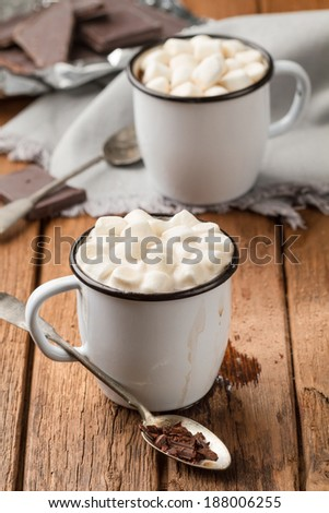 Hot chocolate with marshmallows in two enamel mugs on a wooden table