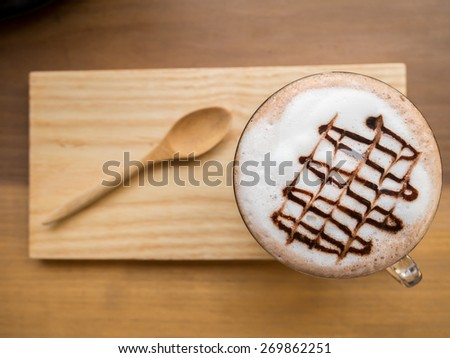 Hot chocolate with milk foam and wooden saucer