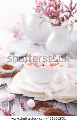Hot chocolate with mini marshmallows with cocoa on white wooden background.