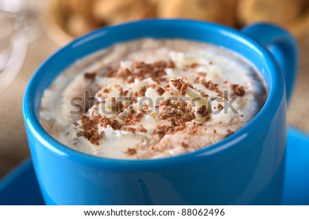 Hot chocolate with whipped cream and chocolate shavings in blue cup with cookies in the back (Selective Focus, Focus on the top of the cream)