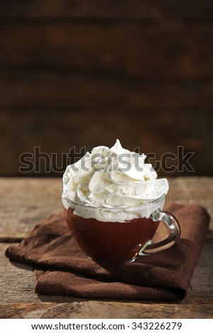 Hot chocolate with whipped cream in mug  on wooden background - stock photo