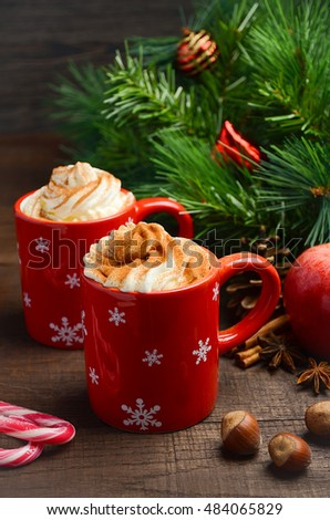 Hot chocolate with whipped cream in red cups. Christmas composition. Selective focus.