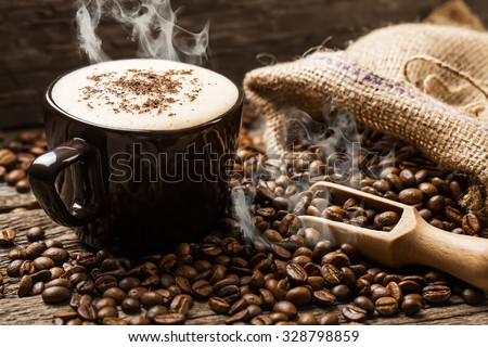 hot coffee and coffee beans on the background of coffee grinders - stock photo