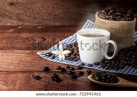 Hot coffee and coffee beans on wooden table background, copy space
