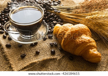 Hot coffee and coffee beans with croissants / for breakfast morning concept