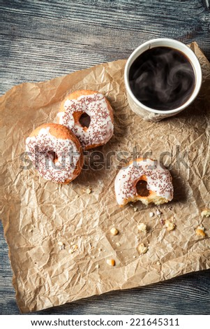 Hot coffee and donuts on paper - stock photo