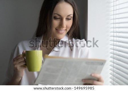 Hot coffee and fresh news. Beautiful young woman reading newspaper and drinking coffee - stock photo