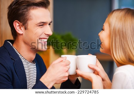 Hot coffee and hot love. Beautiful young couple looking at each other and smiling while enjoying coffee in cafe together  - stock photo
