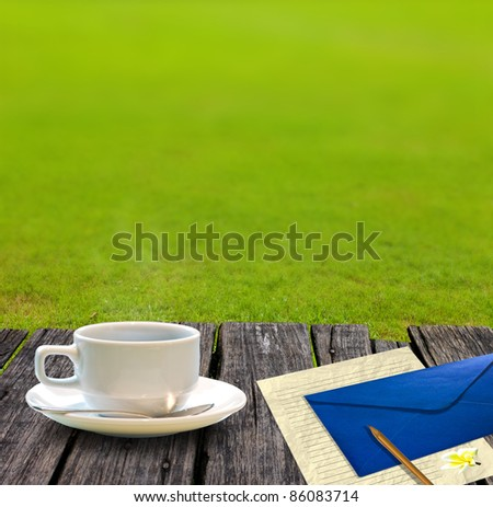 Hot coffee and letter paper on the wooden table with garden background - stock photo