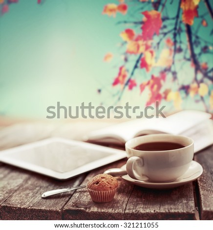 Hot coffee and open book with autumn leaves on wood background - seasonal relax concept - stock photo