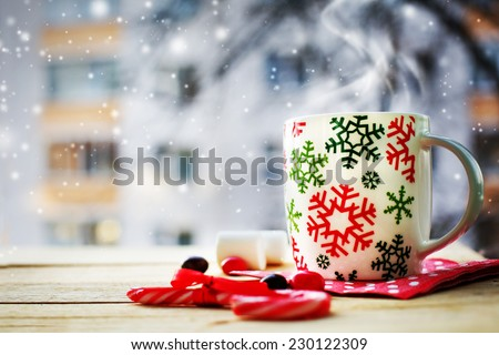 Hot Coffee cup on a frosty winter day window background with candy canes /Christmas holidays background/ Winter cozy background - stock photo