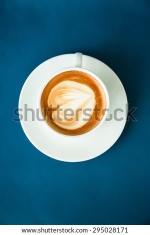 Hot coffee cup on blue leather desk - stock photo